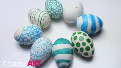 Drawing designs with markers on Easter eggs